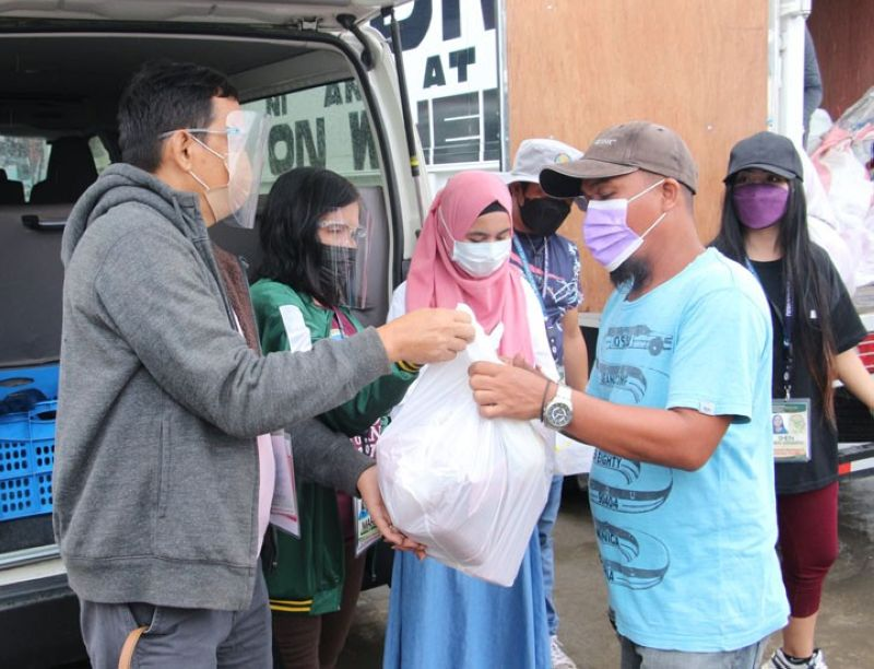 ZAMBOANGA. The Department of Agriculture (DA)-Agribusiness and Marketing Assistance Division (AMAD) conducts an outreach mission Saturday, October 23, that benefits 100 families who are fire victims in Recodo village, Zamboanga City. A photo handout shows a fire victim (with baseball cap) received a pack of relief goods from DA personnel. (SunStar Zamboanga)