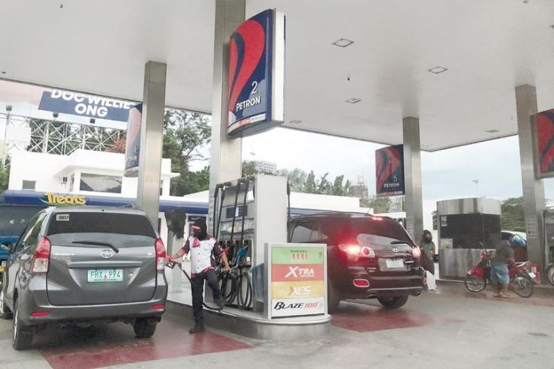 GAS UP. This Oct. 25, 2021 photo shows a gas station worker in Cebu City attending to a motorist to gas up. Fuel prices have increased for several weeks now, hitting consumers and car owners alike. On Monday, the government announced that it will released some P1 billion to fund fuel subsidies to PUV drivers affected by the recent oil price spike. / CSL